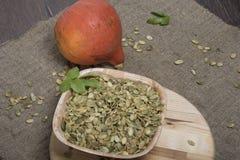 Calabaza, semillas de calabaza en una tabla de cortar redonda Imágenes de archivo libres de regalías