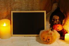 Calabaza, velas y cráneo de la decoración de Halloween con el espacio de la copia en fondo de la pared Fotos de archivo