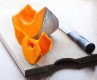 Calabaza y cuchillo cortados en un tablero de madera Fotos de archivo