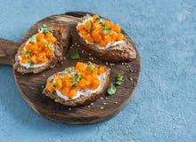 Calabaza y goat& x27; bruschetta del queso de s en una tabla de cortar de madera en fondo azul Fotografía de archivo
