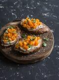 Calabaza y goat& x27; bruschetta del queso de s en una tabla de cortar de madera en fondo oscuro Fotografía de archivo libre de regalías
