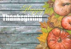 Calabaza y hojas y acción de gracias feliz en la tabla de madera Foto de archivo libre de regalías