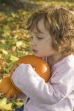 Calabazas adorables del abarcamiento de la niña en un campo del otoño Foto de archivo libre de regalías