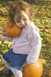 Calabazas adorables del abarcamiento de la niña en un campo del otoño Foto de archivo