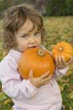 Calabazas adorables del abarcamiento de la niña en un campo del otoño Imagen de archivo libre de regalías