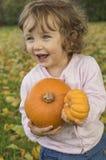Calabazas adorables del abarcamiento de la niña en un campo del otoño Fotografía de archivo libre de regalías