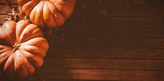 Calabazas anaranjadas con las hojas de otoño en la tabla Foto de archivo