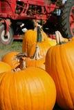Calabazas anaranjadas en una configuración de la granja con el alimentador rojo Fotos de archivo