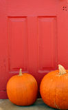 Calabazas anaranjadas y puerta roja Foto de archivo libre de regalías