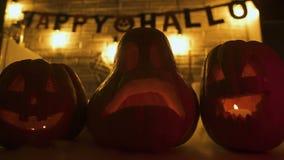 Calabazas asustadizas de la linterna de Jack O con las velas en la tabla, diseño del partido de Halloween almacen de video