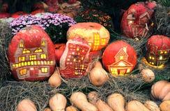 Calabazas de Halloween con la luz dentro de y aún la vida con la porción de flores y de heno Imagenes de archivo