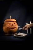 Calabazas de Halloween con un cigarrillo que fuma en su boca La mano sostiene un cenicero Foto de archivo libre de regalías