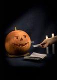 Calabazas de Halloween con un cigarrillo que fuma en su boca La mano sostiene un cenicero Imágenes de archivo libres de regalías