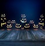 Calabazas de Halloween en un fondo y un piso oscuros de madera Fotos de archivo