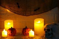 Calabazas de Halloween, velas y cráneo del horror en fondo de la pared Imagenes de archivo