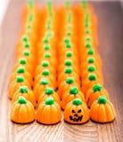 Calabazas de las pastillas de caramelo en fila con el ` de Jack-o - cara de la linterna Fotografía de archivo libre de regalías