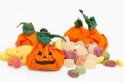 Calabazas de Víspera de Todos los Santos con los caramelos. Calabazas anaranjadas. Fotos de archivo libres de regalías