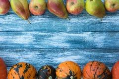 Calabazas, manzanas, peras y hojas de otoño en fondo de madera Imagen de archivo libre de regalías