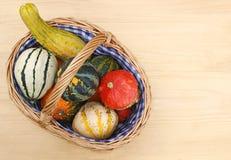Calabazas ornamentales coloreadas multi en una cesta de mimbre fotos de archivo