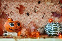 Calabazas pintadas para Halloween, las hojas que caen y los árboles de castaña con las guirnaldas de las luces holiday fotografía de archivo