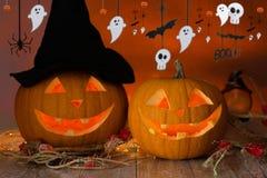 Calabazas talladas en sombrero de la bruja y la guirnalda de Halloween Fotos de archivo libres de regalías