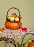 Calabazas y manzanas en cestas en el banco de madera Imagen de archivo