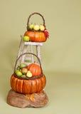Calabazas y manzanas en cestas en el banco de madera Imagenes de archivo