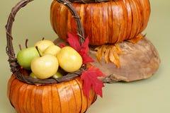 Calabazas y manzanas en cestas en el banco de madera Fotos de archivo libres de regalías