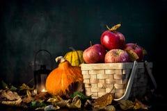 Calabazas y manzanas jugosas rojas en fondo del otoño Fotos de archivo