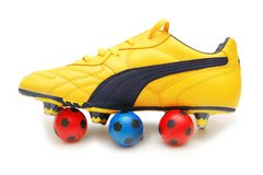 Calçados do futebol e coluna amarelos Fotografia de Stock
