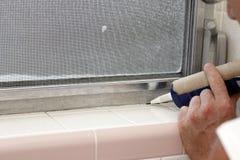 Calafateo de un marco de ventana del cuarto de baño Imagen de archivo libre de regalías