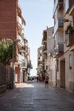 Calafell resort town in Catalonia, Spain. Calafell, Spain - August 13, 2014: Calafell resort town in Catalonia, Spain. Vertical street view with walking ordinary Royalty Free Stock Images