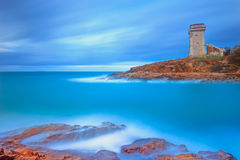 Calafuria Tower landmark on cliff rock and sea. Tuscany, Italy. Long exposure photography. Stock Image