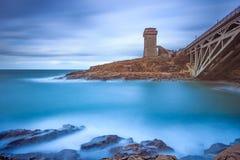 Calafuria-Turmmarkstein auf Klippenfelsen, aurelia Brücke und Meer. Toskana, Italien. Lizenzfreies Stockfoto