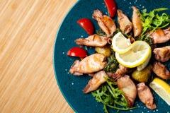 Calamar asado a la parrilla con el limón y las verduras en la placa del color en el restaurante italiano Fotos de archivo libres de regalías