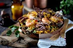 Calamar do marisco, camarão, mexilhões com arroz, ervilhas verdes, pimento, açafrão, gengibre e coentro Foto de Stock