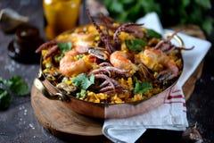 Calamar do marisco, camarão, mexilhões com arroz, ervilhas verdes, pimento, açafrão, gengibre e coentro Fotos de Stock