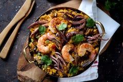 Calamar do marisco, camarão, mexilhões com arroz, ervilhas verdes, pimento, açafrão, gengibre e coentro Fotografia de Stock