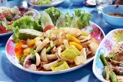 Calamar frito en polvo de curry amarillo en el plato que se sostiene a mano del mA Imagen de archivo