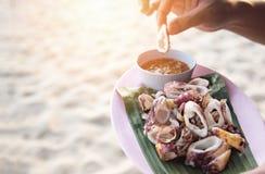 Calamar grelhado no fundo do mar da praia - fatia de calamar na placa com molho de marisco tailand?s dispon?vel fotografia de stock royalty free