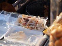 Calamar secado al sol asado a la parrilla cortado en cajas de la espuma Fotografía de archivo