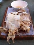 Calamar seco de la parrilla en la placa de madera Imagenes de archivo