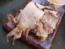 Calamar seco de la parrilla en la placa de madera Imágenes de archivo libres de regalías