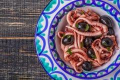 Calamares grelhados do tentáculo decorados com salsa e azeitonas Foto de Stock