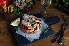 Calamares grelhados, srimps com mexilhões cozinhados, batatas fritas e vinho Imagens de Stock Royalty Free