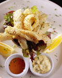 Calamari. Restaurant meal of Peppered Calamari with lemon wedges Stock Photos