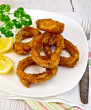 Calamari fried with lemon and fork on plate Royalty Free Stock Photo