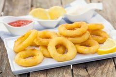 Calamari italian style. Deep fried calamari with lemon and salad on white tray Stock Photos