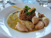Calamari tubes. Pan fried calamari tubes on lime garlic and butter sauce with spiced rice Royalty Free Stock Photo