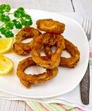 Calamarien stekte med citronen och gaffeln på plattan Royaltyfri Foto